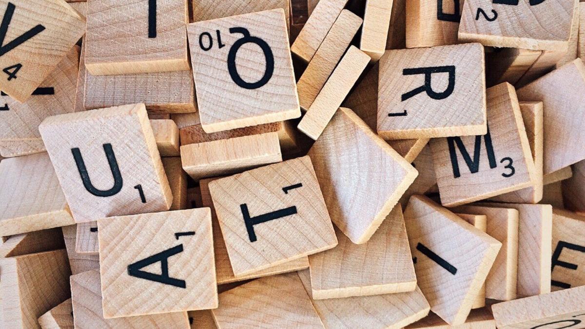 Puisia Scrabble-pelin kirjainlaattoja sekaisin päällekkäin